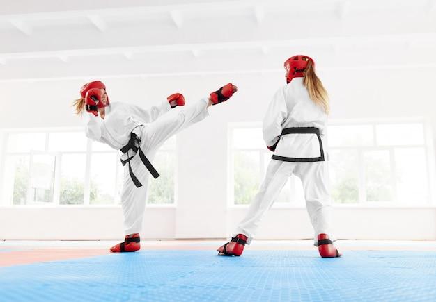 Joven boxeadora luchadora utilizando la técnica de karate kick and punch.