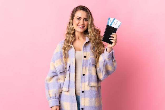 Joven brasileña aislada en rosa feliz de vacaciones con pasaporte y billetes de avión