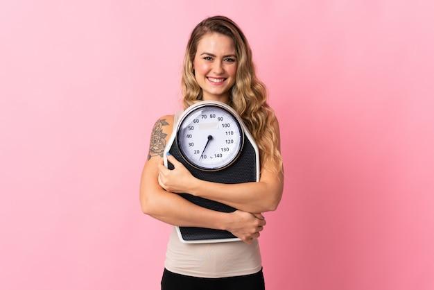 Joven brasileña aislada en rosa con máquina de pesaje