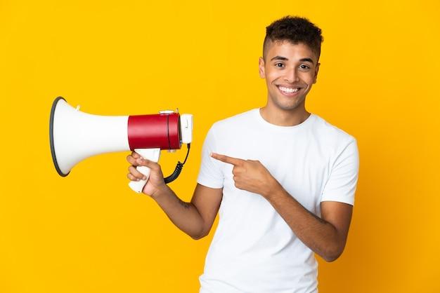 Joven brasileño sobre aislado sosteniendo un megáfono y apuntando hacia el lado