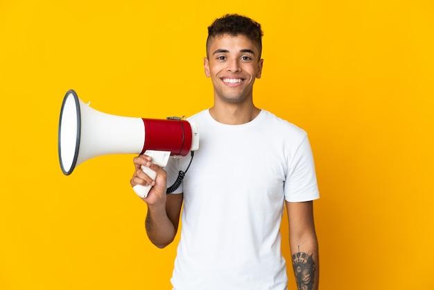 Joven brasileño sobre antecedentes aislados sosteniendo un megáfono y sonriendo mucho