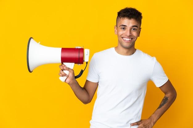 Joven brasileño sobre espacio aislado sosteniendo un megáfono y sonriendo