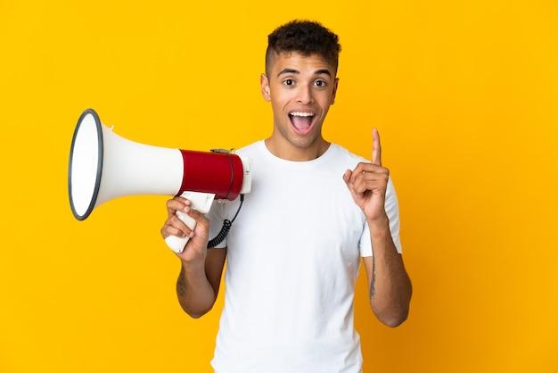 Joven brasileño sobre pared aislada sosteniendo un megáfono y apuntando una gran idea