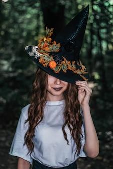 Joven bruja bonita con sombrero negro de cerca en el bosque. whitch cosplay de halloween. procesamiento de arte.