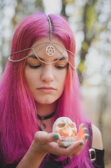 Joven bruja de cabello rosado con una vela de calavera en sus manos, enfoque suave, colores desvaídos