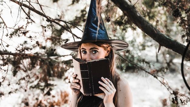 Joven bruja escondida en el viejo libro en el bosque soleado