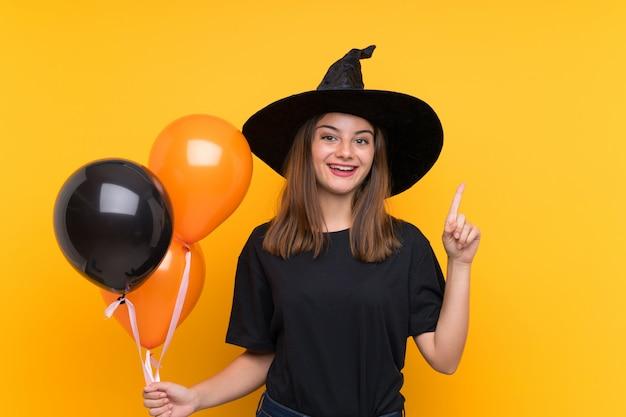 Joven bruja con globos aerostáticos negros y naranjas para fiestas de halloween señalando una gran idea
