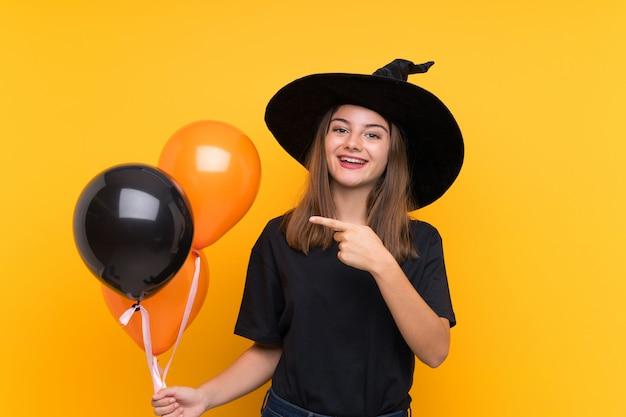 Joven bruja con globos negros y naranjas para fiestas de halloween apuntando hacia un lado para presentar un producto
