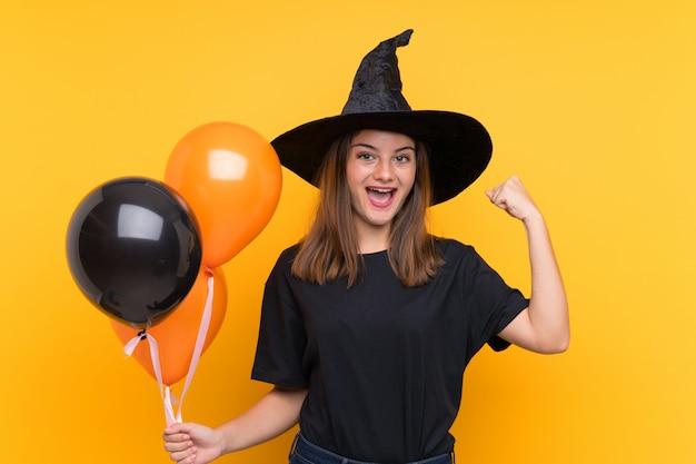 Joven bruja con globos negros y naranjas para fiestas de halloween celebrando una victoria