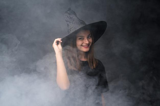 Joven bruja con globos negros y naranjas para fiestas de halloween