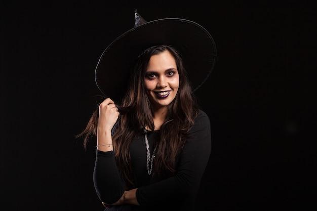 Joven bruja hermosa con un vestido negro y un gran sombrero sonriendo sobre fondo negro. chica guapa lista para halloween vestida como una bruja.