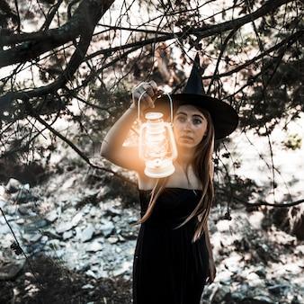 Joven bruja con la lámpara que ilumina el camino en matorral durante el día