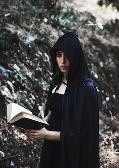 Joven bruja con el libro en matorral