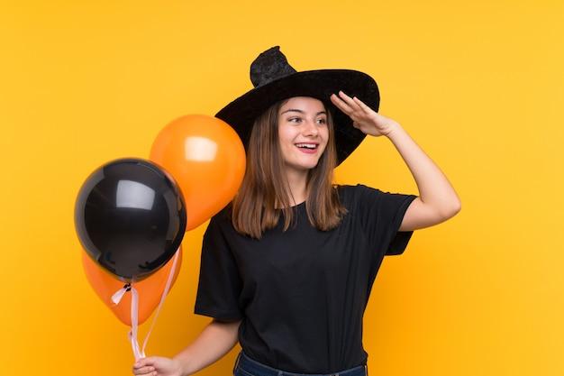 La joven bruja que sostiene globos aerostáticos negros y naranjas para fiestas de halloween se ha dado cuenta de algo y tiene la intención de resolver