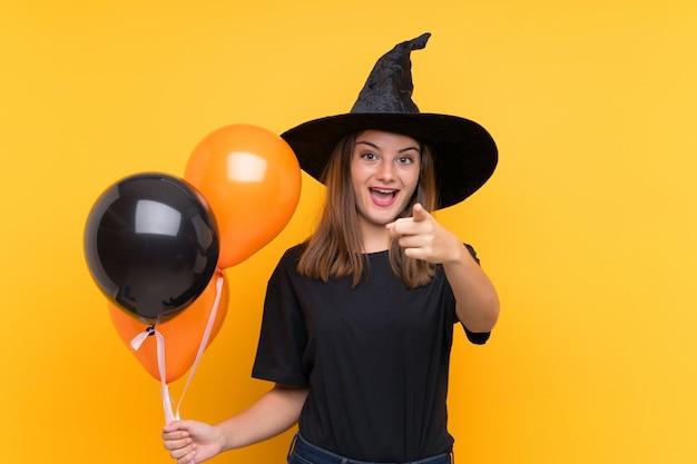 Joven bruja sosteniendo globos de aire negros y naranjas para fiestas de halloween sorprendidos y apuntando al frente
