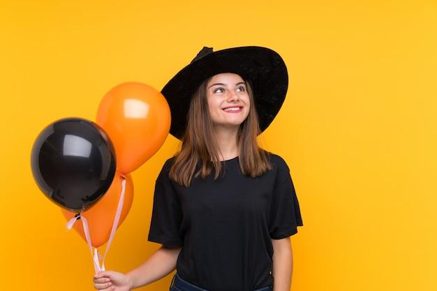 Joven bruja sosteniendo globos negros y naranjas para fiestas de halloween mirando hacia arriba mientras sonríe