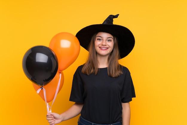 Joven bruja sosteniendo globos negros y naranjas para fiestas de halloween sonriendo mucho