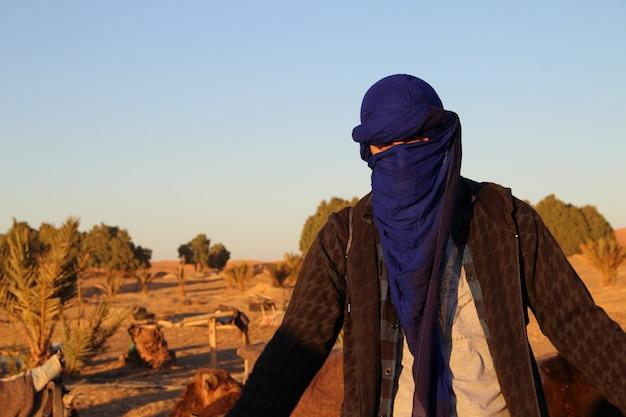 Un joven con la bufanda bereber en el desierto de merzouga