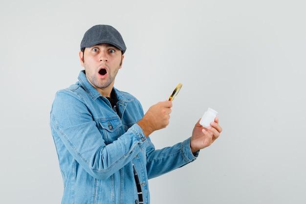 Joven busca frasco de píldoras con lupa en chaqueta, gorra y mirando asustado