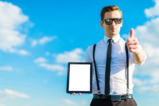 Joven busunessman en camisa blanca, corbata, tirantes y gafas de sol muestra tableta vacía