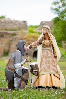 Joven caballero medieval y dama en la hierba verde al aire libre en primavera.