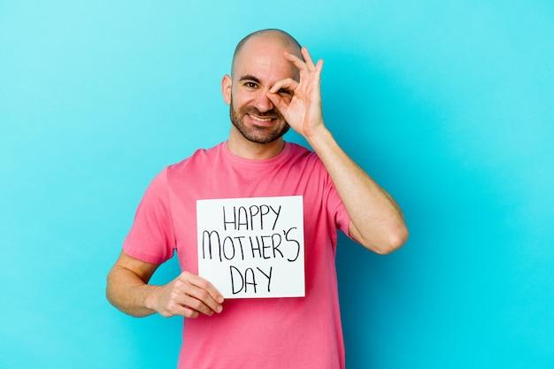 Joven calvo caucásico sosteniendo un cartel de feliz día de las madres aislado en azul emocionado manteniendo el gesto ok en el ojo