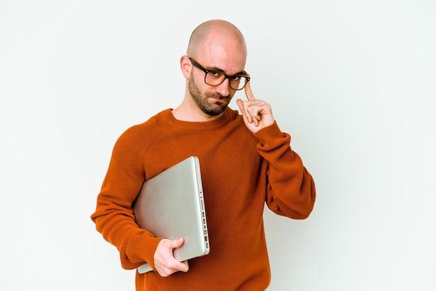 Joven calvo sosteniendo un portátil aislado sobre fondo blanco señalando la sien con el dedo, pensando, centrado en una tarea.