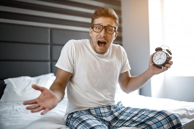 Joven en la cama por la mañana. se durmió de más. guy mantenga el reloj en la mano y mire a la cámara.