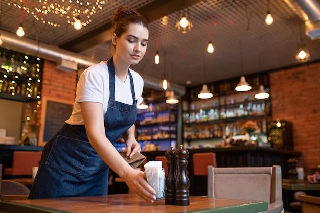 Joven camarera del elegante restaurante poniendo vidrio con un montón de palillos, sal y pimienta en una de las mesas mientras lo prepara para los invitados