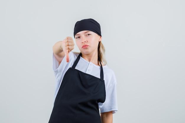 Joven camarera mostrando el pulgar hacia abajo en vista frontal uniforme y delantal.