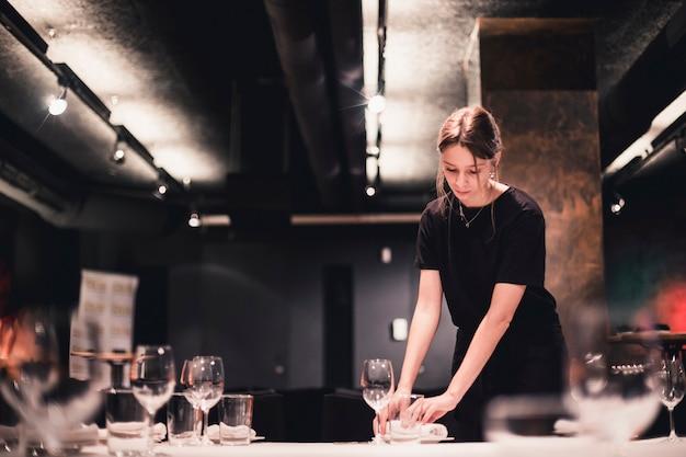 Joven camarera organizar platos en la mesa