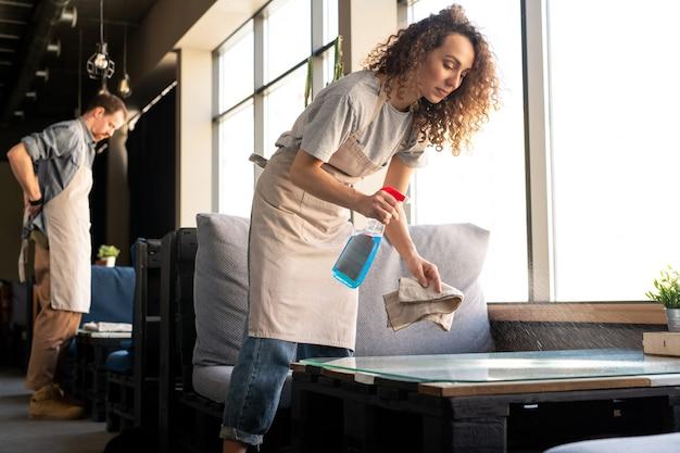 Joven camarera de pelo rizado en delantal rociando detergente mientras bussing mesas en café antes de abrir