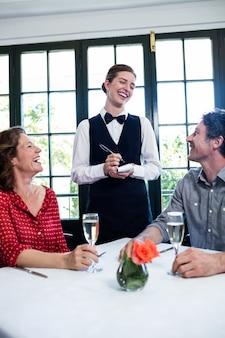 Joven camarera riendo mientras toma una orden de una pareja