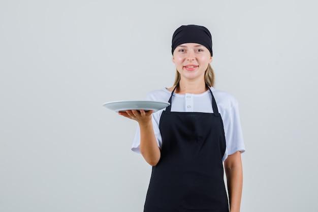 Joven camarera sosteniendo un plato vacío en uniforme y delantal y mirando alegre