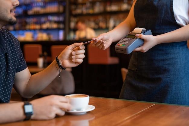 Joven camarera con terminal de pago que devuelve la tarjeta de crédito al cliente masculino después de pagar una taza de capuchino fresco en un elegante restaurante