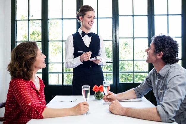 Joven camarera tomando un pedido de una pareja