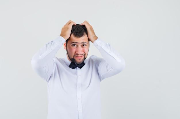 Joven camarero con camisa blanca agarrando la cabeza entre las manos y mirando indefenso, vista frontal.