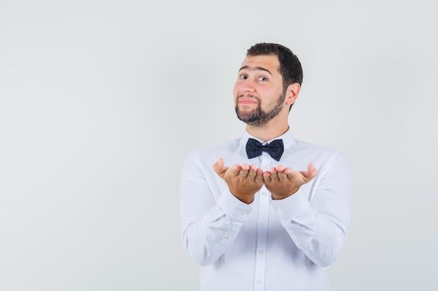 Joven camarero con camisa blanca sosteniendo las palmas abiertas juntas y mirando alegre, vista frontal.