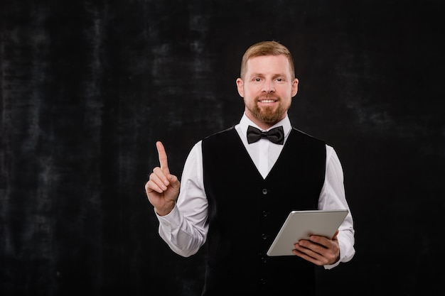 Joven camarero elegante con touchpad apuntando hacia arriba delante de la cámara sobre fondo negro