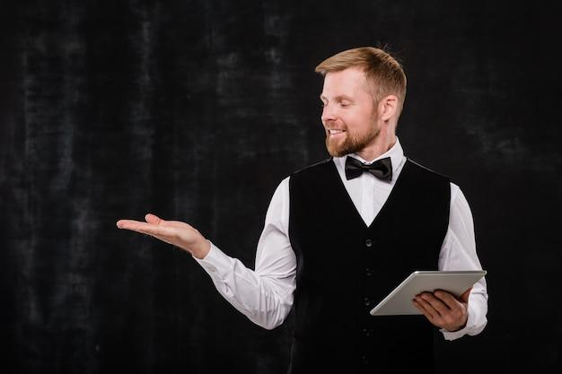 Joven camarero elegante con touchpad mirando cosas imaginarias en su mano mientras está de pie frente a la cámara contra el fondo negro