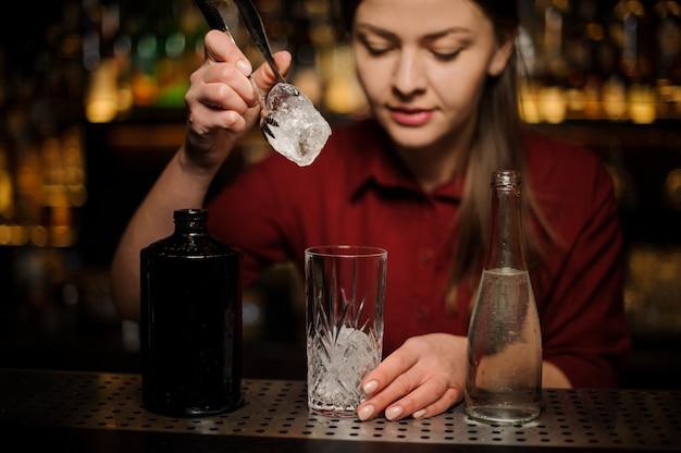Joven camarero hembra poniendo un cubito de hielo en un vaso