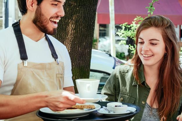Joven camarero sirviendo café a clienta.
