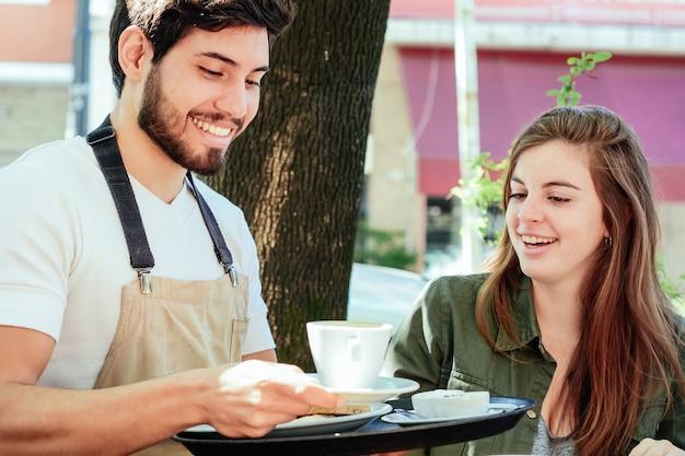 Joven camarero sirviendo café a clienta