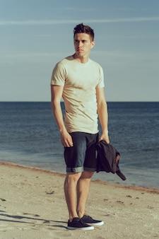 Joven caminando por la orilla del mar