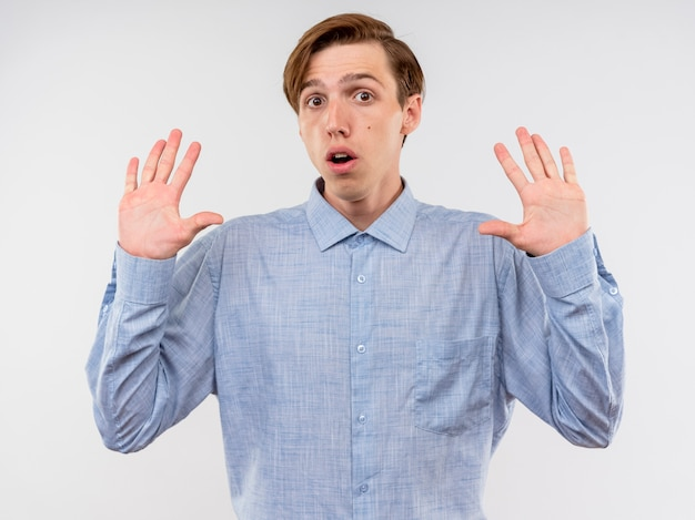 Joven en camisa azul levantando las manos en la rendición de estar asustado de pie sobre fondo blanco.