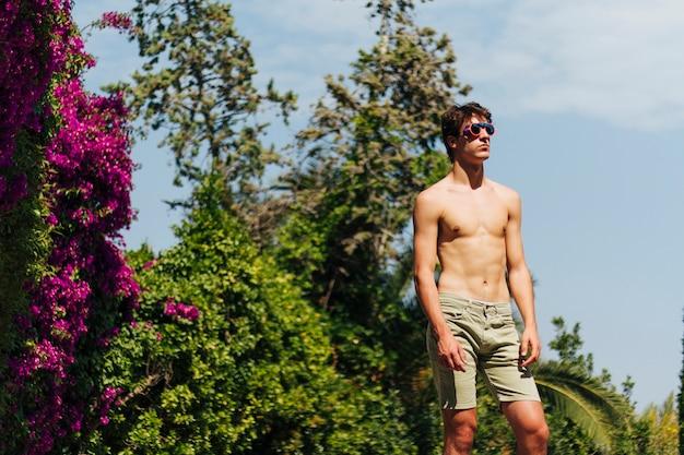 Joven sin camisa con gafas posando en el parque