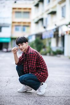 Un joven con una camisa a rayas sentado en la calle