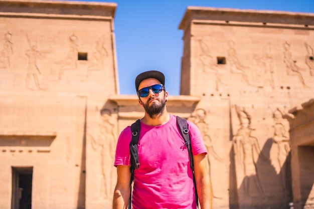 Un joven con una camisa rosa en el templo de filae, una construcción grecorromana, un templo dedicado a isis, diosa del amor. asuán. egipcio