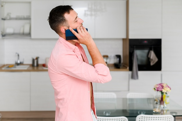 Joven en camisa con teléfono inteligente en la oreja