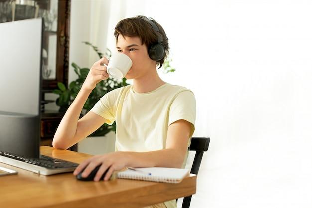Joven en una camiseta amarilla trabaja en casa en la computadora. chatear en línea. trabajo remoto a través de internet en aislamiento durante la cuarentena del coronavirus. persona de libre dedicación